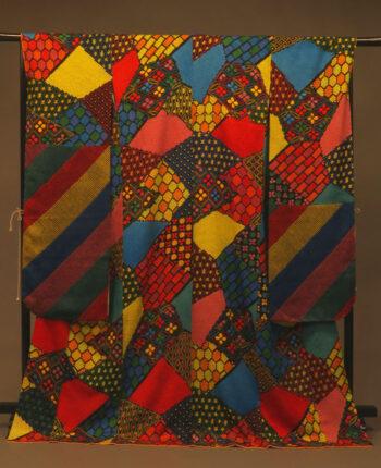 袖をつぎ足した振袖。色鮮やかな幾何学模様を全面に敷いたがらの着物に虹色の袖をつぎ足した着物。
